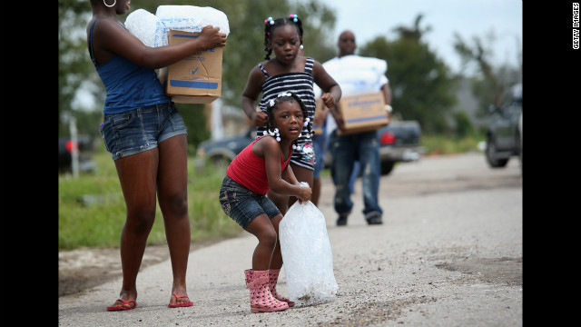  A family carries bags of ice and boxes of food from an aid distribution center for victims of Isaac in New Orleans. The center was one of three in the city operated by the military, offering handouts to residents, many of whom still have no electricity due to the storm. 