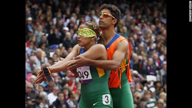 Brazil's Terezinha Guilhermina, left, prepares with her coach at the start of the women's 200-meter T11 race.