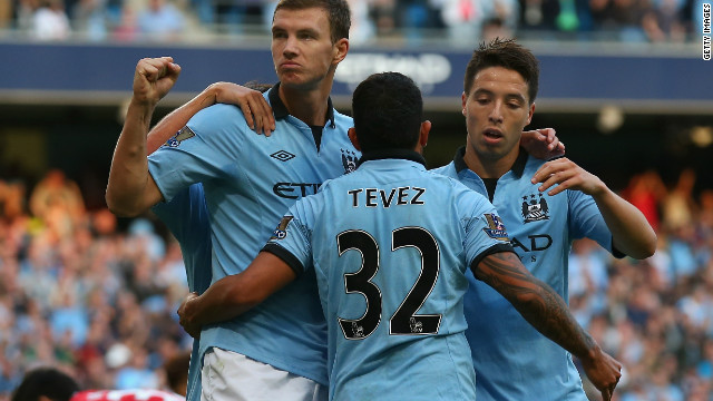 Carlos Tevez celebrates with goalscorer Edin Dzeko and Samir Nasri in Manchester City's 3-1 win over QPR. 