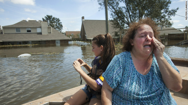 Plaquemines Parish resident Angela Serpas reacts after seeing her flooded home for the first time following Hurricane Isaac, as her daughter Lainy takes pictures, in Braithwaite, Louisiana, on Saturday, September 1. At least five deaths in Louisiana and two in neighboring Mississippi were blamed on Isaac, and residents of the two states still suffered from power outages and widespread flooding on Saturday, authorities said. 