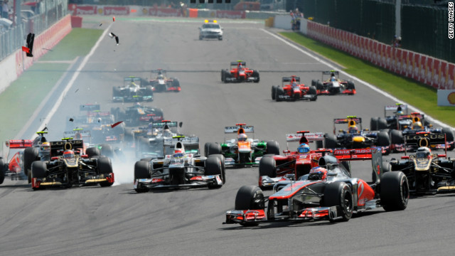 Jenson Button leads while his McLaren teammate Lewis Hamilton has made contact with the rear of Romain Grosjean's Lotus. 