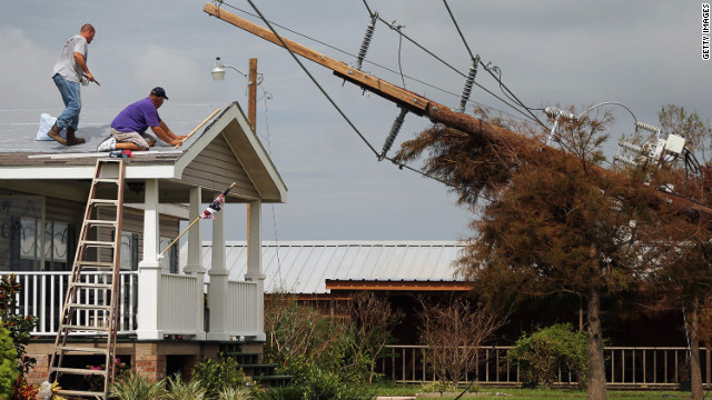 Workers repair the roof of a home as downed power lines caused by Hurricane Isaac lean onto a tree in lower Plaquemines Parish on Sunday, September 2. Isaac is blamed for at least four deaths in Louisiana and Mississippi after making landfall last week as a Category 1 hurricane. Hundreds of thousands in the region were without power early Sunday.