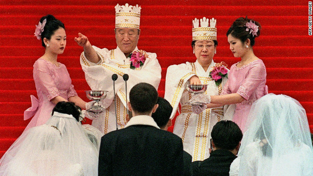 Moon and his wife bless the brides and the grooms during the ceremony in Seoul. Followers of the Unification Church are sometimes referred to as &quot;Moonies.&quot;