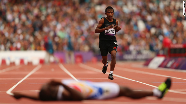 Filomeno Soares of East Timor competes in the men's 400-meter - T38 heats at Olympic Stadium. The winner, Venezuela's Omar Monterola, lies on the floor after crossing the finish line.