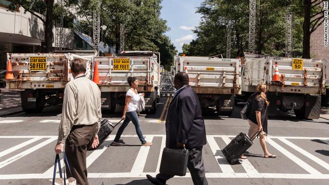 Pedestrians walk past dump trucks Sunday that are serving as barriers.