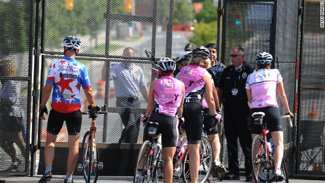 Bicycle riders are stopped by police guarding the perimeter of the Time Warner Cable Arena on Monday.