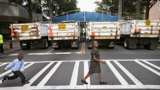 Children cross the street in front of a row of dump trucks used as a barricade near the Bank of America headquarters in downtown Charlotte on Sunday.