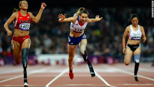 France's Marie-Amelie le Fur, center, lunges over the finish line to win the women's 100-meter T44 final as April Holmes, left, of the United States finishes third.
