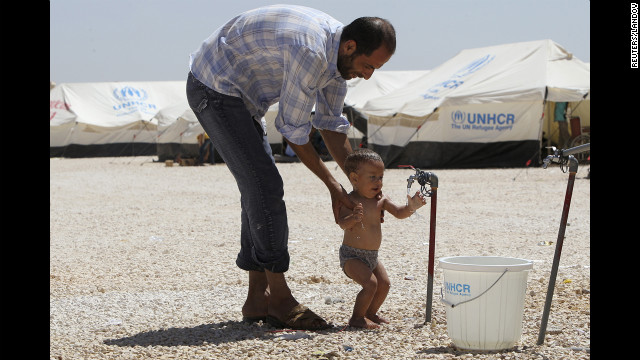 A Syrian refugee bathes his child. Water is provided several times daily by water trucks, but supplies of fresh water are very limited and the needs of the refugees are putting pressure on local communities which already experience water shortages.