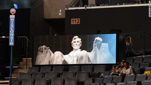 People in the Wisconsin delegation area sit in front of a digital image of the Lincoln Memorial hours before the start of the convention on Tuesday.