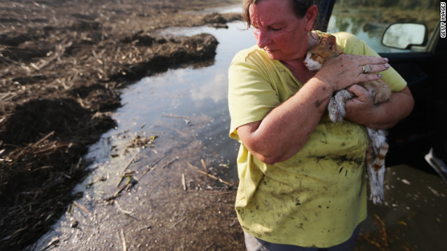 Melanie Martinez holds the family cat, now renamed Isaac, after salvaging items from her family's flooded home in Braithwaite on Monday, September 3. Martinez, along with her husband and her mother, was forced to ride out the storm in their Plaquemines Parish home when their car broke down.