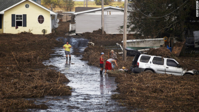 Melanie Martinez, left, and family members salvage items from their flooded home Monday.