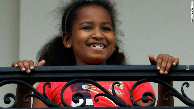 Sasha watches her Dad from the Truman Balcony after he arrives on the south lawn of the White House via Marine One on May 14, 2009.