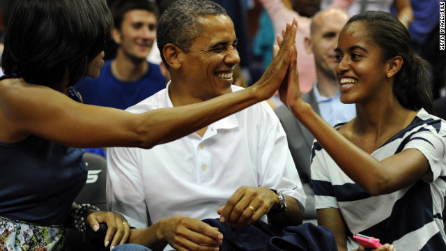President Barack Obama shares a laugh with his wife Michelle and daughter Malia, as the U.S. Senior Men's National Team plays Brazil in a pre-Olympic exhibition basketball game on July 16, 2012, in Washington.
