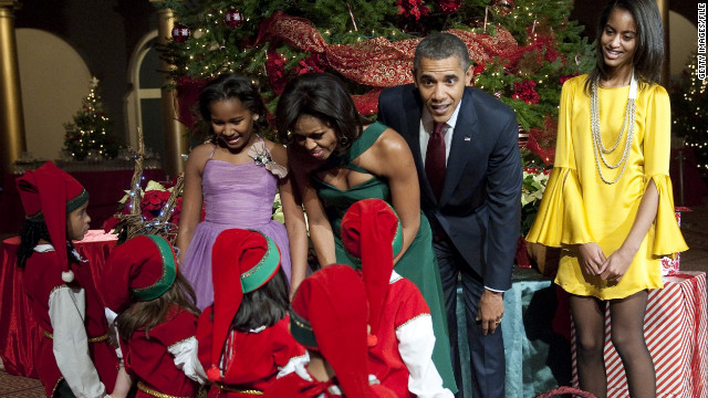 "The first family greet children dressed as elves prior to the taping of ""Christmas in Washington,"" at the National Building Museum in Washington on December 11, 2011."