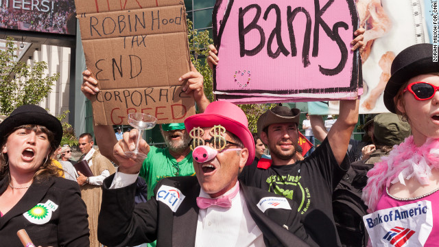 Costumed protesters yell about corporate greed during the convention.