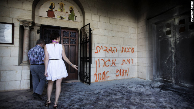 Tourists look at a burnt door as they walk past grafitti sprayed on the wall of the Christian Catholic Latrun monastery on Tuesday.