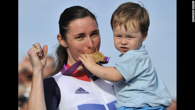 Britain's Sarah Storey, left, bites her gold medal as her nephew Gethin Crayford holds it on the podium after she won the women's individual C4-5 road race cycling final on Thursday.