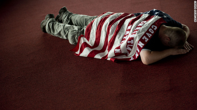 "Nathan Conley, draped in an American flag with the phrase ""Covenant Christian Nation,"" prays during a prayer service at the Verizon Wireless Amphitheatre in Charlotte on Sunday."