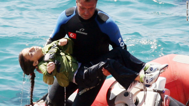  A diver carries a young girl who was rescued after a boat capsized Thursday in the Aegean Sea off western Turkey.