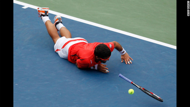 Tipsarevic slips on the court while attempting a return shot.