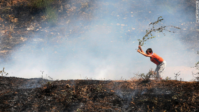 An Albanian boy uses a branch to try to put out a blaze near the city of Memaliaj, Albania, on August 28, 2012. Albania has battled multiple forest fires since June after several heat waves and months of drought.<!-- --> </br>