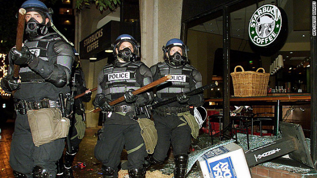 <strong>1999:</strong> Riot police march past a damaged Starbucks coffee shop during demonstrations against the World Trade Organization Summit in Seattle on November 30, 1999. Thousands of activists aimed to disrupt the WTO.