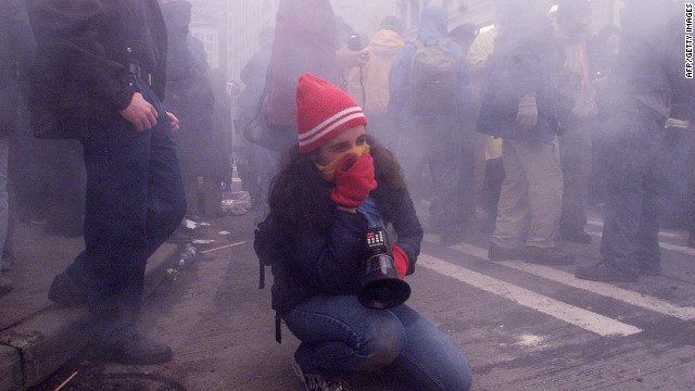 &lt;strong&gt;1999: &lt;/strong&gt;A demonstrator covers her mouth with a scarf to protect herself from tear gas after street clashes with riot police in downtown Seattle during WTO protests.