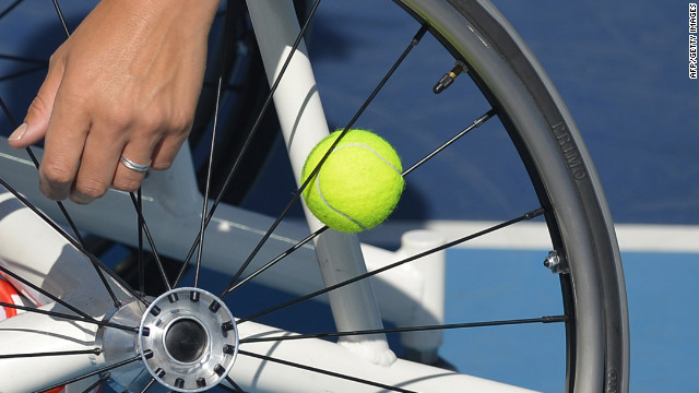 Netherlands' Esther Vergeer keeps a spare ball in the spokes of her wheelchair as she plays Netherlands' Aniek Van Koot in the women's singles wheelchair tennis final on Friday.