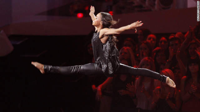 "U.S. Olympic athlete Gabby Douglas leaps in the air during Alicia Keys' performance of ""Girl on Fire."""
