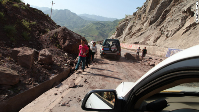 Vehicles make their way slowly along the road after rocks tumbled in Yiliang.