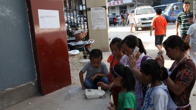 Survivors gather to make phone calls by a street in Yiliang.