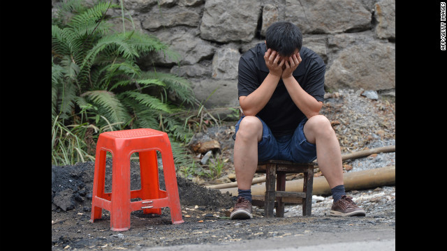 A man reacts as he sits outside his house on Saturday after a series of earthquakes. 