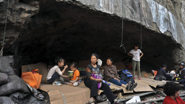  Residents rest in a stone cave, their temporary shelter, in Yiliang on Saturday. 