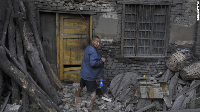 A resident returns to his damaged home on Saturday, September 8, after staying out for a night following an earthquake in Yiliang, Yunnan province.
