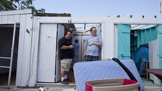  People inspect the damage in their rental cabanas.
