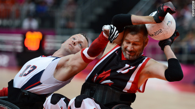 No. 13 Derrick Helton of the United States attempts to get the ball from No. 13 Jared Funk of Canada during Saturday's mixed wheelchair rugby semifinal match between the U.S. and Canada.