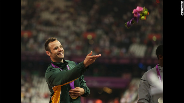 Gold medalist Oscar Pistorius of South Africa throws a bouquet of flowers on the podium during the medal ceremony for the men's 400-meter T44 final Saturday, September 8, at the 2012 Paralympic Games.