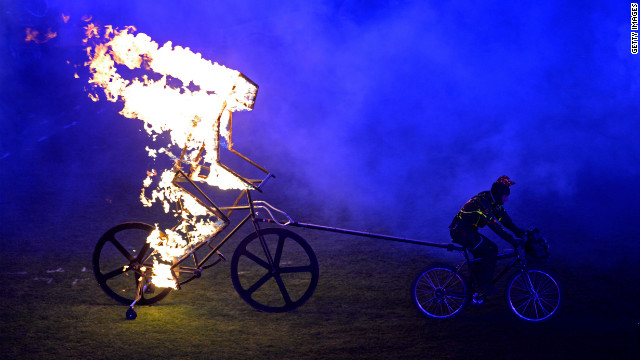 A flaming figure of a cyclist enters the arena.