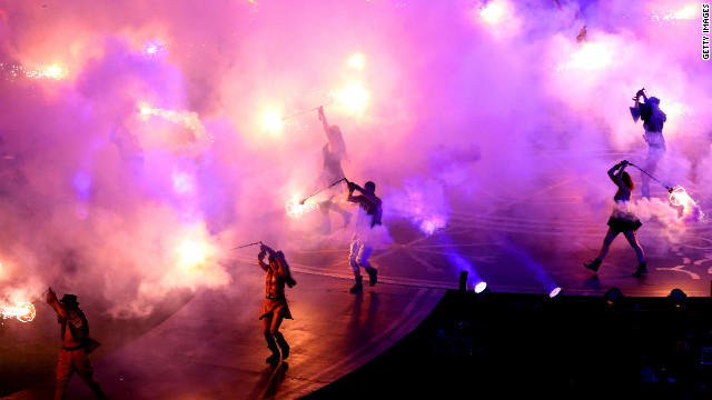 Smoke and flames fill the air as dancers perform.