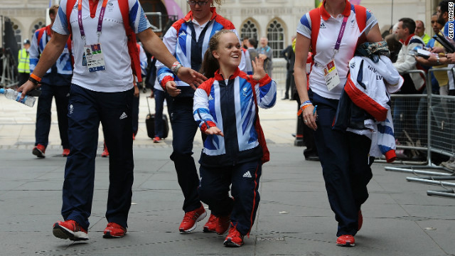 "Swimmer Eleanor Simmonds, known as ""Ellie"", waves to the crowds as she walks along during the Victory Parade. Simmonds won two gold medals and a silver at the Paralympics."