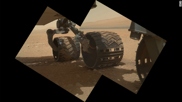 This view of the three left wheels of NASA's Mars rover Curiosity combines two images that were taken by the rover's Mars Hand Lens Imager on Sunday, September 9, the 34th Martian day of Curiosity's work on Mars. In the distance is the lower slope of Mount Sharp.