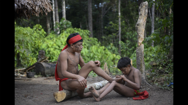 A Yanomami child cleans the feet of another member of the tribe.
