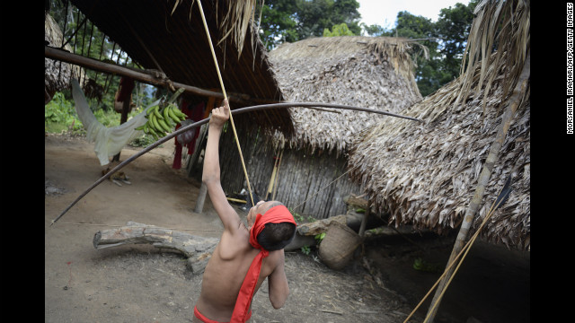 A Yanomami child child tests his bow and arrow.