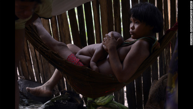 A Yanomami woman rests with her baby.