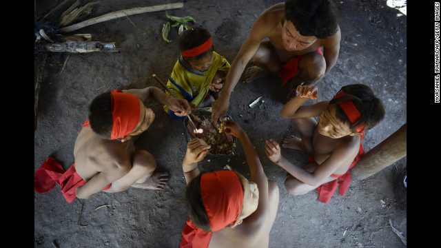 A Yanomami family gathers to eat a meal.