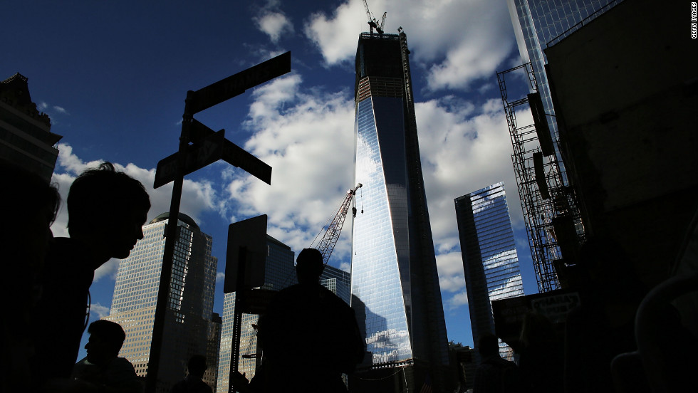 Pedestrians walk by One World Trade Center on the eve of the 11th anniversary of the September 11 terrorist attacks on Monday, September 10 in New York City. Work proceeds at the former site of the World Trade Center Twin Towers.