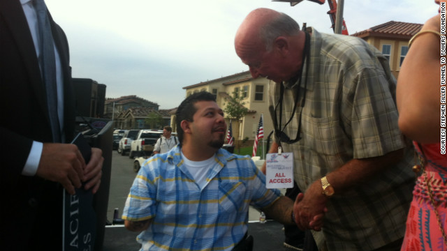 Dominguez greets Ned Wallace of Wallace Air Cargo, who donated $450,000 toward the purchase the home, at the presentation of his new 'smart' home.