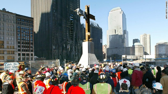 New York City firefighters and construction workers surround the steel cross at Ground Zero during a prayer service held at 8:46 am to commemorate the sixth-month anniversary of the September 11 terrorist attacks on March 11, 2002 in New York City.