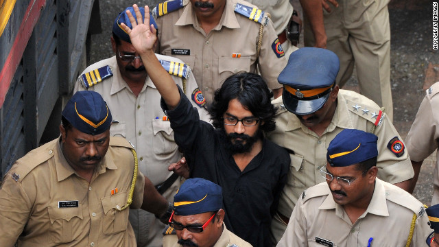 Indian cartoonist Aseem Trivedi, who has been arrested on sedition charges, raises his hand outside the Metropolitan Magistrate court in Mumbai on Monday